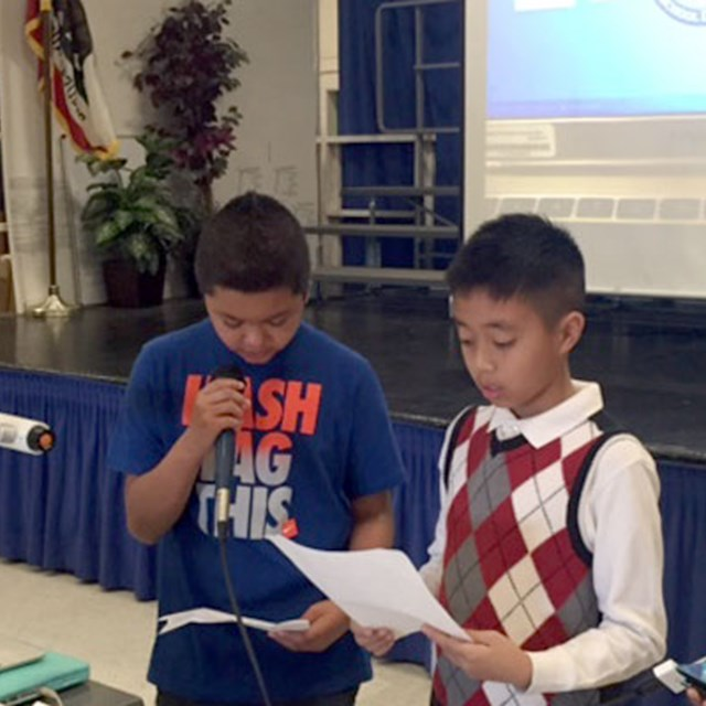 Three students learn public speaking skills while presenting for the class.